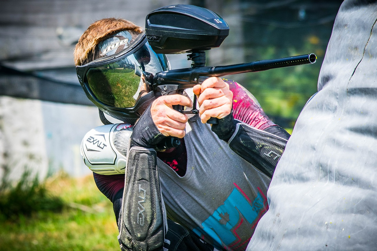 paintball player aiming from paintball gun