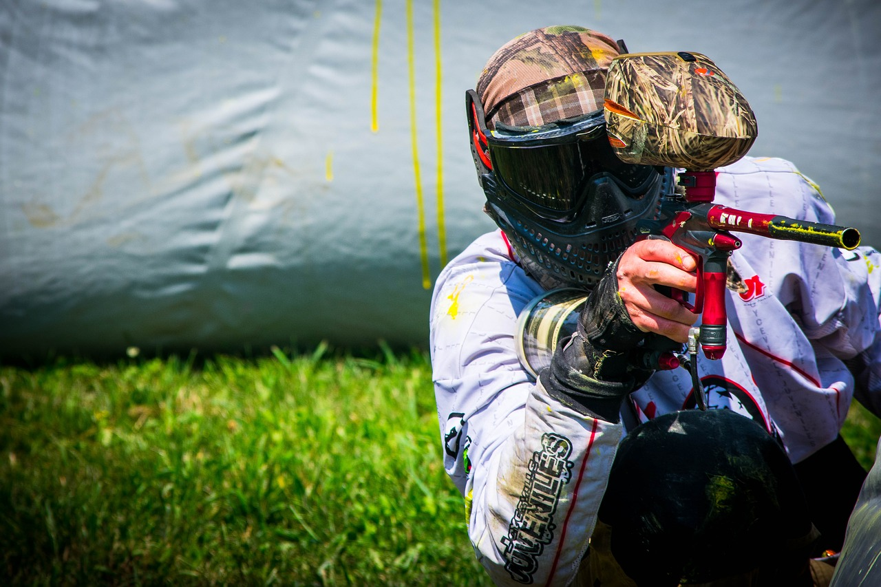 Man wearing a helmet aiming a paintball gun